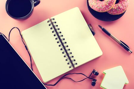 Open notebook and cup of coffee with donut on a pink background. Tinted picture. Stock Photo