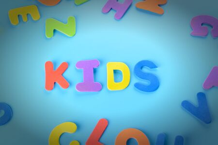 Beautifully laid out inscription kids of multi-colored letters. Background with vignette.