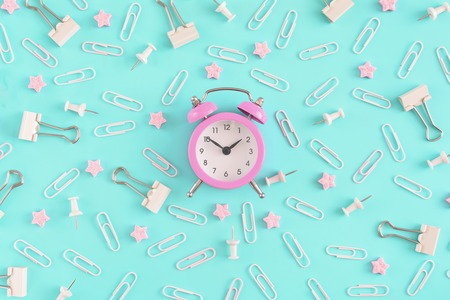 Stationery chaotically scattered on a bright blue background. White paper clips, clerical buttons and small pink stars in disorder . In the center is a small pink alarm clock. Picture from the top. Stock Photo