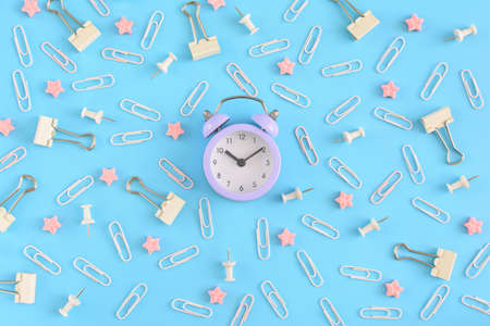 Stationery chaotically scattered on a blue background. White paper clips, clerical buttons and small pink stars in disorder . In the center is a small lilac alarm clock. Picture from the top.