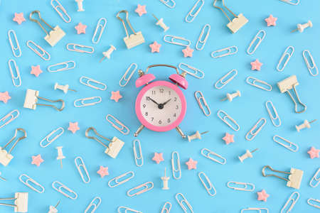 Stationery chaotically scattered. White paper clips, clerical buttons and small pink stars are in disorder on a blue background. In the center is a small pink alarm clock. Picture from the top.
