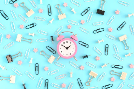 The stationery is chaotically scattered on a blue background. White and black paper clips, clerical buttons are in disarray. In the center is a small pink alarm clock. Picture from above. Stock Photo