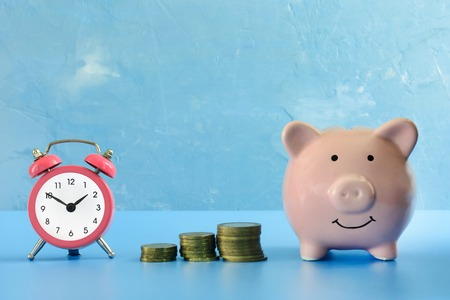 On a dark blue background photographed piggy bank, next to her a small pink alarm clock and three stacks of coins. Preservation of savings.