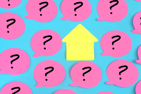 Pink stickers with question marks drawn on them on a blue background. In the center there is an empty yellow sticky piece in the form of a house. Photo from the top. Imagens