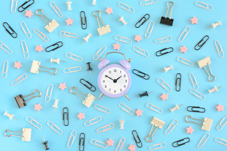 A little lilac alarm clock, in the center of the clutter of office supplies. White and black paper clips, clerical buttons and small pink stars are randomly scattered on a blue background.