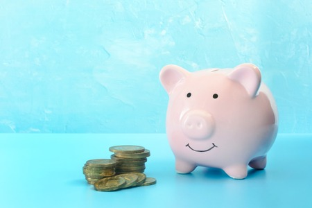 Piggy bank on a light turquoise background. Near to three stacks of coins. The symbol is the accumulation and conservation of money. Stock Photo