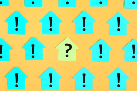 Stickers in the form of houses on a bright yellow background. On the turquoise sticky notes are written exclamation marks. In the center on the yellow sticker is a question mark. Stockfoto