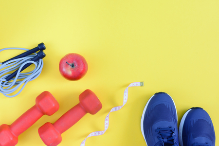 Fitness background with place for text. Sneakers, skipping rope, apple and dumbbells on a yellow background.