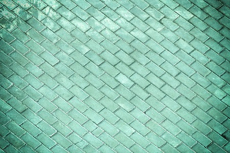 Photo on top of the road paved with sidewalk tiles. Empty background with vignette, texture of masonry