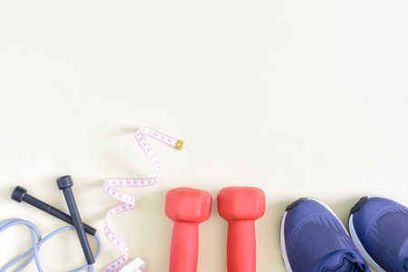 A model with a place for text on a sports theme. Fitness background. Dumbbells, skipping rope, sneakers are located on a light background. 写真素材