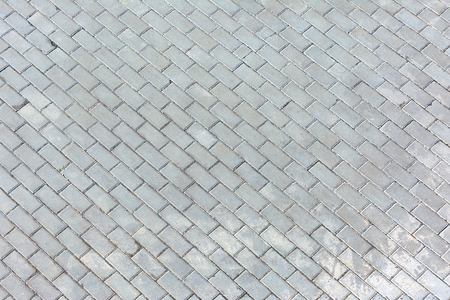 Photo on top of the road paved with sidewalk tiles. Blank background with, masonry texture of light gray bricks. Stock Photo
