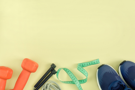 A model with a place for text on a sports theme. Fitness background. Dumbbells, sneakers, skipping rope and centimeter tape are located on a light background. Toned photo. 写真素材
