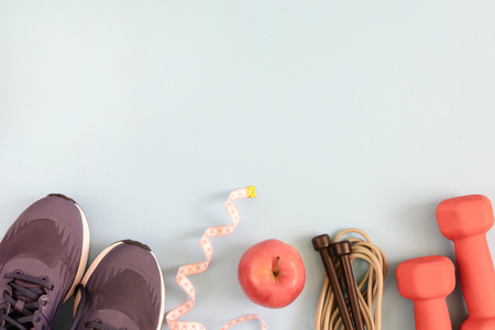 Fitness background with place for text. Sneakers, skipping rope, apple and dumbbells on a pale blue background. Beautiful layout.