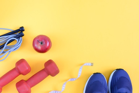 A model with a place for text on a sports theme. Fitness background. Dumbbells, sneakers, a skipping rope and a red apple are located on a bright yellow background. Picture from the top. 写真素材