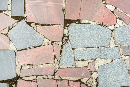 Abstract background with a texture of a stone mosaic. Large gray and pale red granite fragments are chaotically lined. .