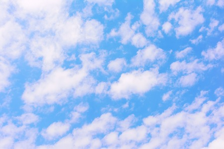 A bright blue sky with lots of small white clouds. Beautiful bright background. 写真素材