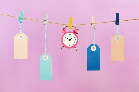 On the ropes on the clothespins are hung empty blue and pink labels. In the center is a small alarm clock. Concept, time to buy. Layout on a pink background. Archivio Fotografico