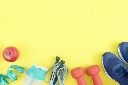 Sports equipment on a yellow background. Dumbbells, rope, bottle and sneakers are beautifully spread out. Fitness background with space for text.