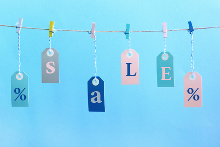 Labels hang on the rope with attached clothespins. They inscription SALE. Stock Photo