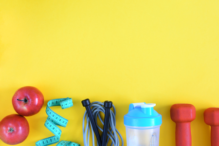 Fitness background with place for text. Bright layout. Sports equipment on a yellow background.