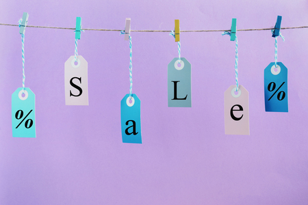 Labels hang on the rope with attached clothespins. They inscription SALE. Photo on a lilac background. Stok Fotoğraf