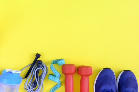 On a yellow background, the sports equipment was photographed. Copy space. Beautiful fitness background with place for text.