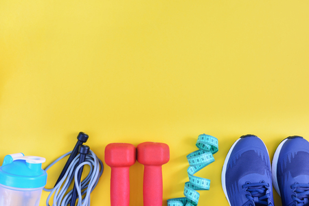 On a yellow background photographed sneakers, skipping rope, dumbbells and a bottle. Copy space. Fitness background with place for text. 写真素材