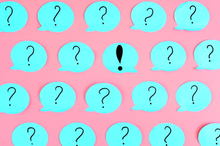 On the pink background is a sticker with an exclamation point. Around him are glued many blue stickers with question marks. Photo from the top. Concept, the question of attention.