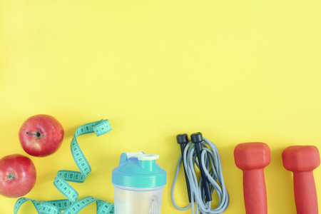 On a bright yellow background lie sneakers, dumbbells, a skipping rope and two apples. Fitness background. A photograph of sports equipment from above.