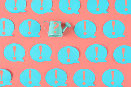 On a pink background, many blue stickers with exclamation marks are pasted. Among them there is a small blue watering can with a question mark. Zdjęcie Seryjne