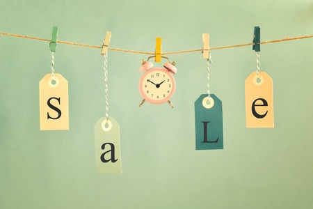 On a light blue background on the rope hang labels labeled SALE. In the center is a small pink alarm clock. Concept, time for sales.