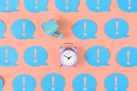 On a pink background blue stickers with exclamation marks are pasted. Among them there is a blue watering can and a small alarm clock. An unusual concept, attention to leakage time.