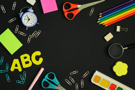 On a black background, school and office supplies are chaotically arranged. In the center there is an empty space for text or an inscription. Pictures on top, mock up.