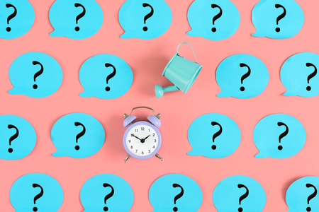 On a pink background, many blue stickers with question marks are pasted. Among them, a alarm clock and a blue watering can. An unusual concept, the issue of time leakage.