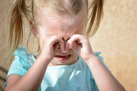 Una niña llora y se frota los ojos con las manos. Histeria infantil.