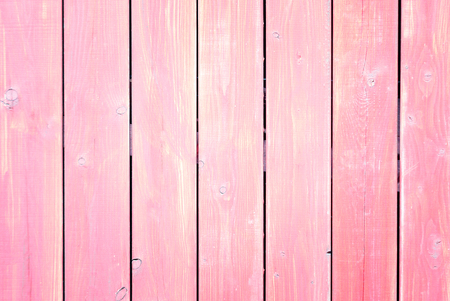 Fence of boards painted in pink. Light background with a texture of wooden slats.