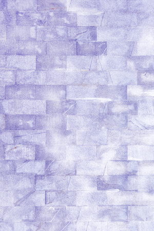 Wall of an unusual light lilac brick. The texture of the brickwork is scratched and cracked. 免版税图像