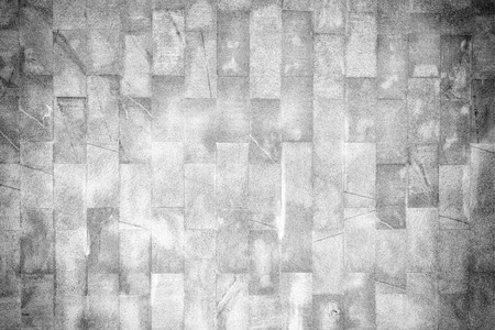 A wall of unusual gray brick. The texture of the brickwork is scratched and cracked. Background with vignette.