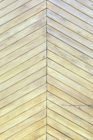 Beautiful background with a texture of thin wooden boards. A wall of pale yellow diagonal slats.