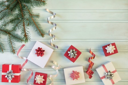Christmas composition of red and white gift boxes, bows and ribbons. A branch of the Christmas tree. Place for text, copy space.
