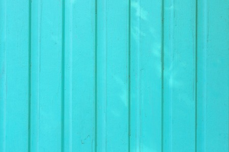 Background of smooth boards painted brightly turquoise paint. Texture with stains of paint.