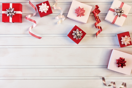 Christmas composition. Small red and white gift boxes with bows, spirals of ribbons. Blank background, copy space.