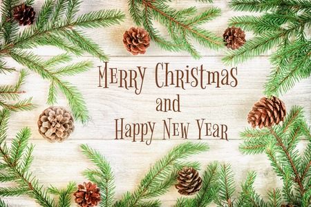 Christmas composition, frame. Spruce branches with cones, laid out in a circle. In the center is the inscription Merry Christmas and Happy New Year.