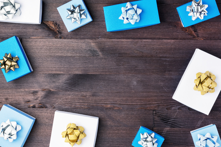 Blue and white gift boxes with decorative bows are laid out on a dark wooden background. In the center is Kopi Space. Festive photo.