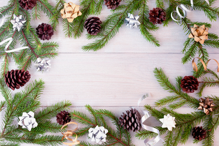 Spruce branches decorated with bows, ribbons and cones laid out in the form of a frame.