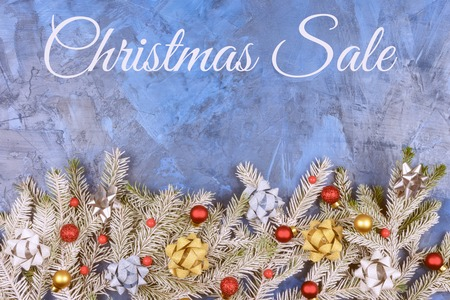 Spruce branches are covered with hoarfrost and decorated with red Christmas balls and silver and gold bows. Christmas composition with the words Christmas Sale, on a dark blue background.
