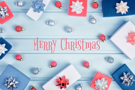 In the center of the inscription Merry Christmas blue background. Red, white and blue gift boxes with bows and Christmas balls are lined up in a circle.