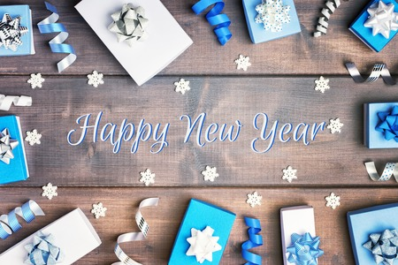 Small blue and white boxes with bows, ribbons and snowflakes, arranged in a circle. Christmas composition with the inscription Happy New Year on wooden background.