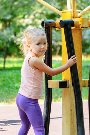 Little girl with blond hair on the sports field.