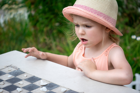 A little girl with blond hair plays homemade checkers of pebbles. Stockfoto